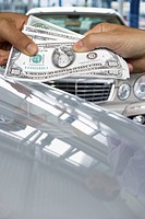 Hands exchanging one hundred dollar bills over luxury cars
