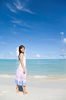 Portrait of a young woman standing on beach, smiling and looking back, Saipan, USA
