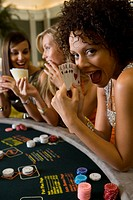 Woman showing poker hand of five aces at casino table