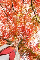 Girl standing under tree with autumn leaves (thumbnail)