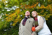 Couple wearing scarves and standing in front of trees (thumbnail)