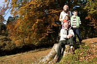 Portrait of grandparents and grandkids in grass with autumn leaves (thumbnail)