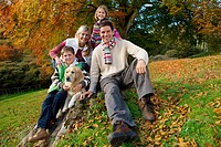 Portrait of family and dog sitting on tree stump in woods