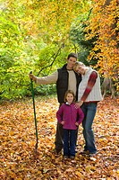 Portrait of family with rake standing in autumn leaves