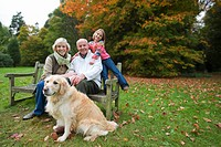 Portrait of grandparents, granddaughter, and dog sitting on bench in park