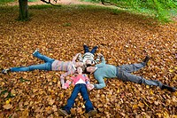 Family holding hands and laying in autumn leaves