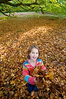 Portrait of girl holding autumn leaves