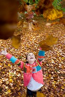 Girl throwing autumn leaves in air