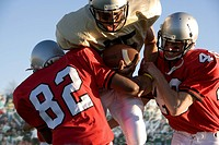 Defenders tackling running back carrying football