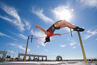 Female athlete jumping over bar, low angle view lens flare