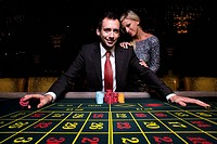 Woman by man gambling at roulette table, portrait, low angle view