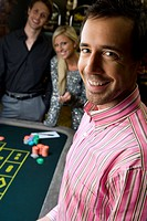 Young man by friends gambling at roulette table, smiling, portrait, close_up