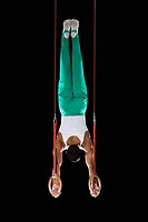 Male gymnast performing handstand on gymnastic rings, rear view
