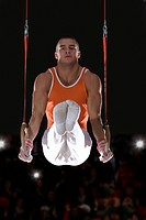 Male gymnast performing on gymnastic rings, portrait, low angle view (thumbnail)