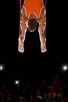 Male gymnast performing on gymnastic rings, rear view