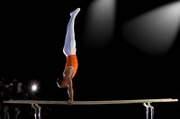 Male gymnast performing handstand on parallel bars, side view (thumbnail)
