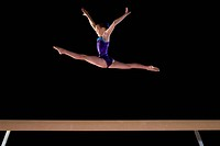 Young female gymnast 9-11 performing on balance beam, low angle view (thumbnail)