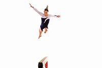Female gymnast performing jump on balance beam, low angle view