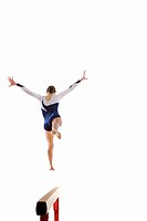Female gymnast performing jump on balance beam, rear view (thumbnail)