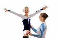 Young female gymnast 9_11 on balance beam with teacher, smiling, portrait