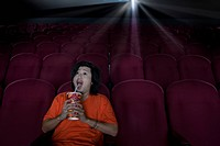 Man with drink in empty cinema making face (thumbnail)