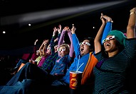Audience in cinema wearing 3D glasses, arms raised, low angle view (thumbnail)