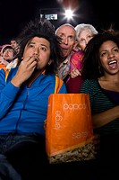 Audience in cinema, man with popcorn, close_up, low angle view