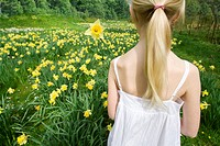 Young girl holding yellow daffodil