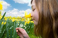 Young girl smelling yellow daffodil
