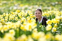 Young girl sitting in field of yellow daffodils