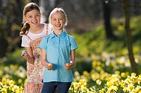 Two young girls holding decorated Easter eggs in field of daffodils