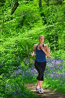 Woman running through field of bluebell flowers
