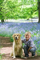 Boy and dog posing in field of bluebell flowers