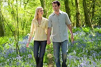Couple walking in field of bluebell flowers