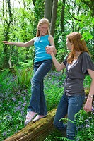 Mother and daughter playing on log among bluebell flowers