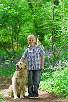 Boy and dog posing in forest among bluebell flowers
