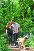 Couple and dog walking in forest among bluebell flowers