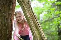 Girl peeking through tree trunk