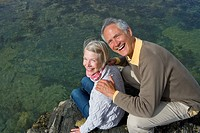 Portrait of senior couple sitting on rock, high angle view