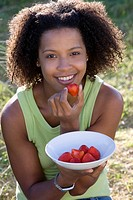 Portrait of young woman eating strawberry