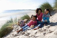 Mother sitting with daughters on beach