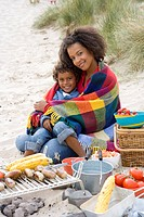Portrait of mother sitting with son on beach