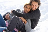 Portrait of mixed race couple hugging in snow (thumbnail)