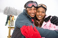 Mixed race couple hugging in winter setting, couple in background