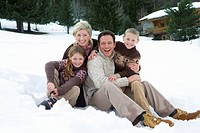 Portrait of young family sitting in snow