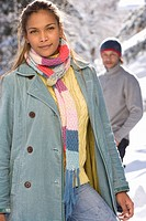 Portrait of young woman standing in snow, man in background