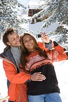 Mixed race couple taking photo of each other in snow