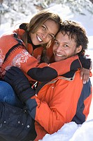 Portrait of mixed race couple sitting in snow