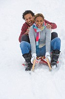 Happy mixed race couple sledding down snow slope