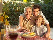 Three generation family of men by dining table portrait